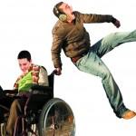 Junge im Rollstuhl mit Laptop, junger Mann mit Kopfhörern spring in die Luft