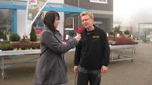 Eine Schülerin interviewt einen Gärtner vor dessen Laden