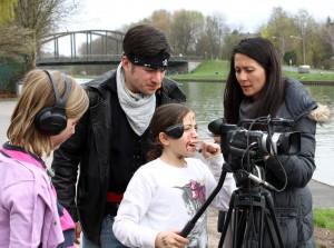 Zwei Medientrainer und zwei Kinder arbeiten mit einer Kamera