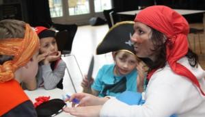 Eine Medientrainerin ist als Piratin geschminkt und zwei Piraten-Kinder