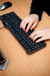 Hände über einer Tastatur beim Tastschreiben