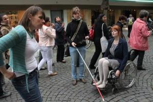 eine Rollifahrerin und eine Sehbehinderte