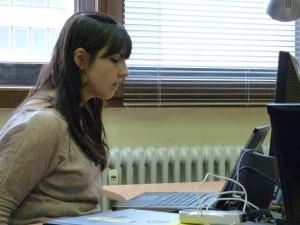 Frau sitzt vor einem Laptop und steuert diesen mit Kopfbewegungen.