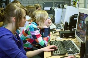 Mädchen sitzen vor Computern und recherchieren