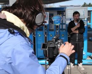 ein junger Mann vor Zapfsäulen an einer Tankstelle wird gefilmt