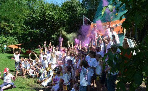 Teilnehmer/innen einer Ferienaktion des Jugendhauses Sürth in weißen Shirts reißen jubelnd die Arme in die Höhe und werfen dabei lilafarbenes Pulver in die Luft