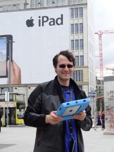 Person mit iPad steht vor Apple Werbung am Potsdamer Platz