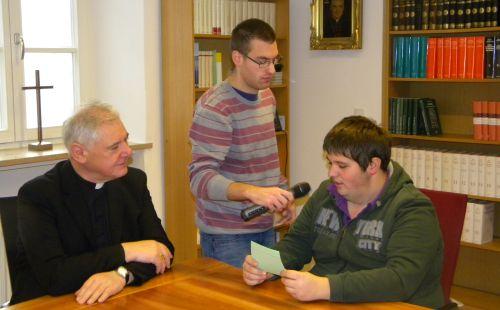 """Zu Gast bei dem damaligen Regensburger Bischof, Dr. Gerhard Ludwig Müller: Pierre Ziebarth (rechts) stellt seine Fragen, u. a.: """"Wer kümmert sich eigentlich um Sie?"""" Ulrich Macht bedient das Mikrophon. (Quelle: Carl Prämaßing)"""