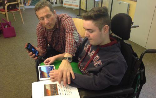 Der Leiter der iBand, Patrick Schäfer, hilft einem Schüler mit dem Notenmaterial dabei, seine Instrumentalstimme zu spielen.
