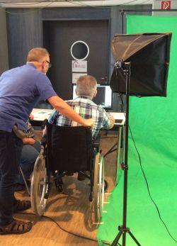 Fotoaufnahme vor dem Greenscreen: Ein Teilnehmender im Rollstuhl wird in Position geschoben