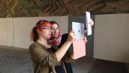 2 Frauen filmen in einer Unterführung mit iPads