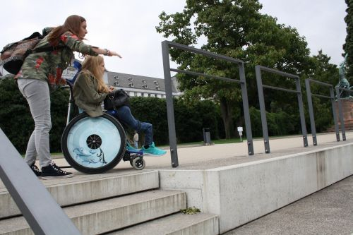 Rollstuhlfahrer-Fußgänger-Tandem oben auf einer Treppe