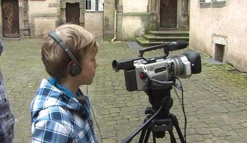Seitenansicht von Jungen mit Kopfhörern vor Videokamera