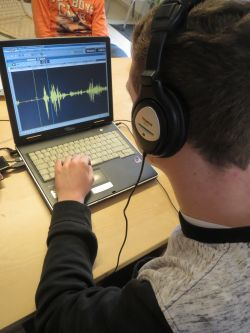 Junge mit Kopfhörer (Hinteransicht) bedient Schnittprogramm am Laptop