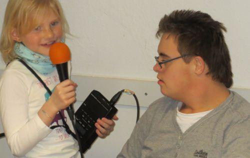 Mädche mit Mikrofon interviewt  Jungen mit Down Syndrom