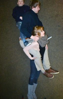 Optische Täuschung: Es sieht aus, als würde ein Mädchen einen sehr großen und einen sehr kleinen Jungen Huckepack tragen.