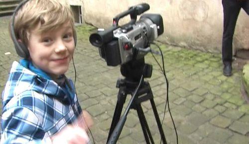 Junge vor Videokamera, lächelndes Gesicht zum Betrachter.