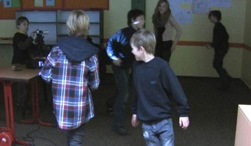 """Kamerafangen: Kinder laufen im Klassenzimmer herum, eine Kamera versucht sie zu """"erhaschen"""""""