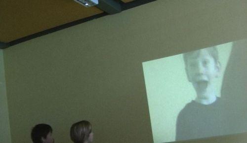 """Kamerafangen: Das gebeamte Gesicht eines von der Kamera """"gefangenen"""" Schülers auf Leinwand."""