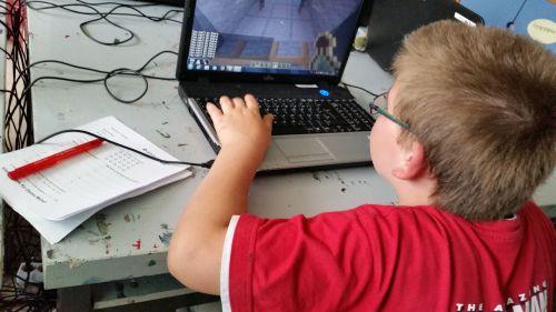 Junge spielt am Computer, neben sich einen Bewertungsbogen