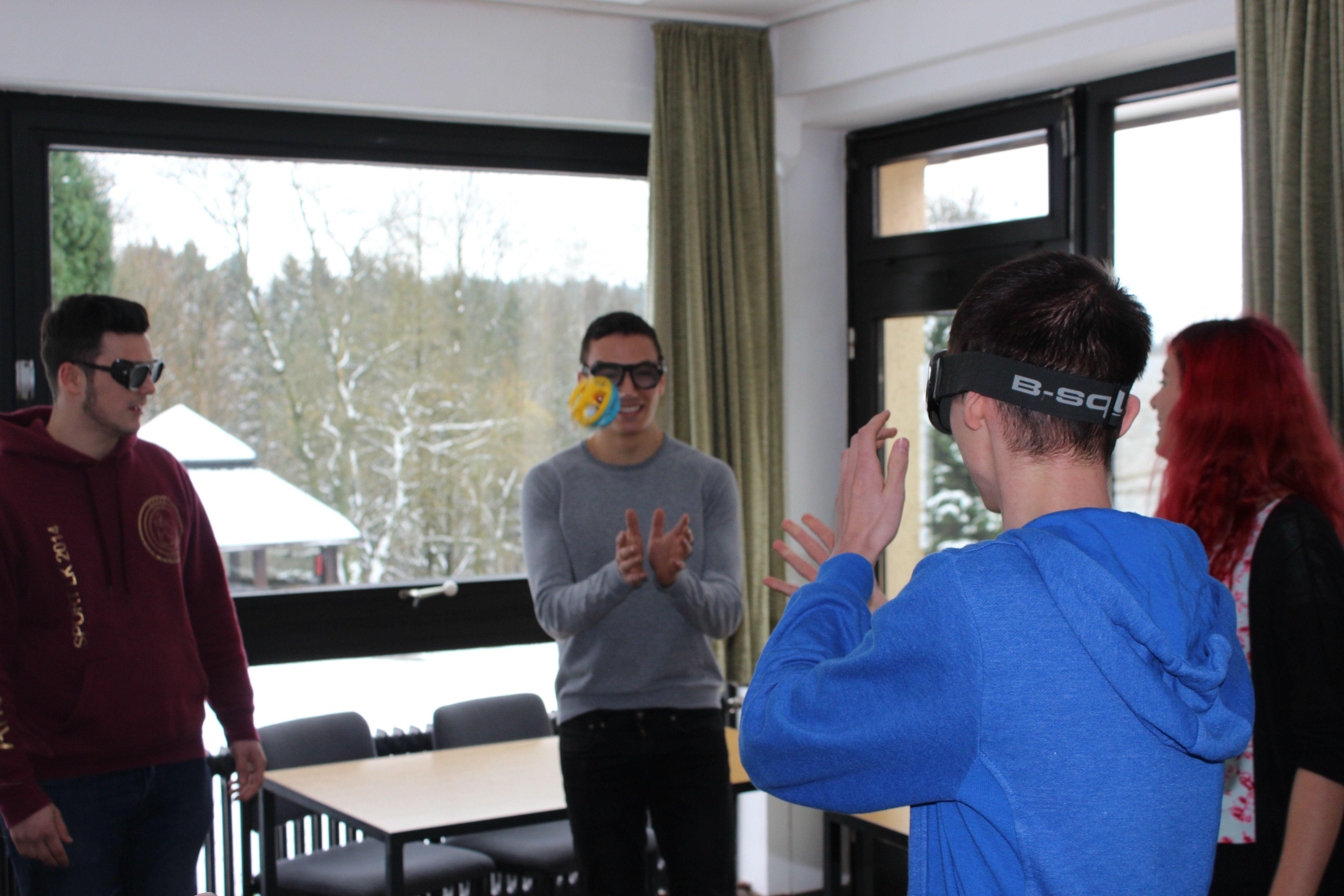 4 Jugendliche mit Brillen, die Sehbehinderungen simulieren, werfen sich einen Klingelbeil zu