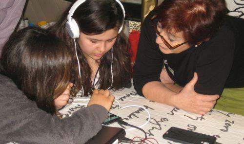 Zwei Mädchen - eins davon mit Kopfhörern - und eine Frau mit Brille beugen sich über ein Tablet.
