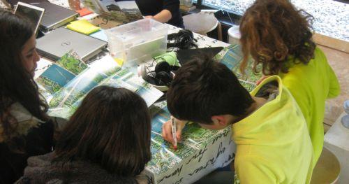 Kinder über Landkarten gebeugt, Laptops und Tablets sind zu sehen.
