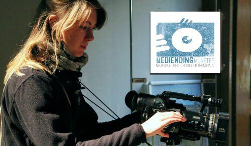 """Frau mit Kamera vor einem Schild mit der Aufschrift """"Mediending Münster - Medienkulturelle Bildung Bennohaus"""""""