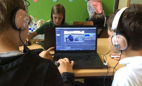 Teilnehmende des Filmprojekt mit Kopfhörern vor dem Laptop beim Filmschnitt
