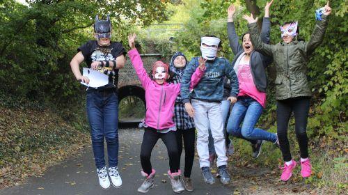 4 Jugendliche mit Masken springen in die Luft