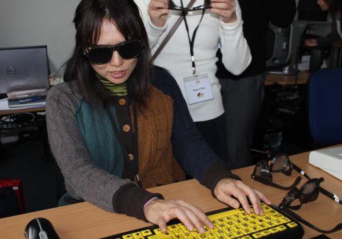 Japanische Frau mit Sehbehinderungsimulationsbrille und einer Spezialtastatur für Sehbehinderte