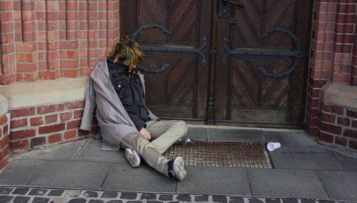 Screenshot aus dem Film Dasein: Ein zusammengesunkener Bettler vor einem Kircheneingang