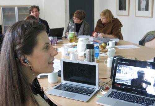 Dozentin Rose Jokic vor Laptops, mit In-Ear-Kopfhörern, lächelnd: Im Hintergrund Fachtags-Teilnehmende