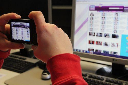 Nahaufnahme: Zwei Hände mit Kamera fotografieren eine Bildschirmseite
