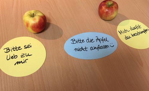 Zwei Äpfel, drei Zeittel mit der Aufschriften: Bitte sei lieb zu mir, Bitte nicht anfassen, Mich darfst du beschimpfen