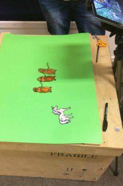 Greenscreen auf Pappkarton mit Figuren Einhorn und den drei Affen