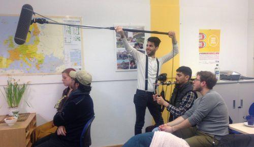 Junge Menschen unterschiedlicher Herkunft arbeiten mit Videokamera und Aufnahmegerät