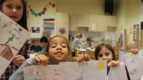 Kinder in einem Klassenraum zeigen stolz ihre Zeichnungen vor