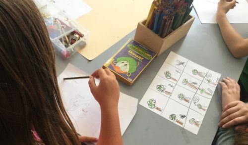 Schreibtisch mit Malutensilien und Kind beim Malen