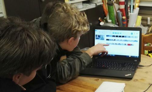 Jungen vor Laptop beim Filmschneiden