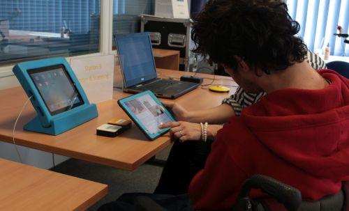 Eine Frau bedient ein Tablet, vor ihr ein Mann im Rollstuhl
