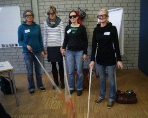 Vier Frauen mit Simulationsbrillen und Blindenstock in einem Raum