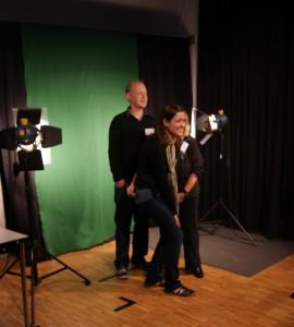Ein Mann und zwei Frauen werden vor einem grünen Hintergrund fotografiert