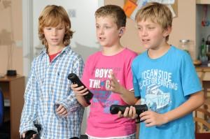 Drei Jungen spielen mit einer Spielekonsole
