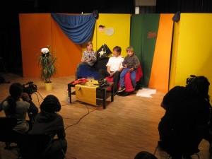 Kinder sitzen vor einem bunten Hintergrund und werden gefilmt
