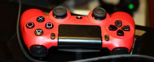 roter Computerspiele-Controller mit schwarzen Knöpfen