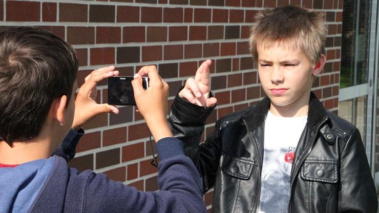 Ein Junge fotografiert, der andere gebärdet das Fingeralphabet