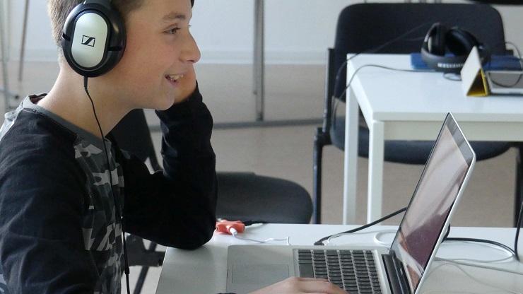 Junge mit Kopfhörer vor Laptop