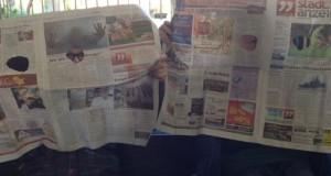 Zwei Kinder-Detektive hinter einer Zeitung mit Löcherausschnitten für Augen