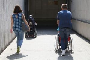 Rollstuhlfahrer und Fußgänger in einer Unterführung